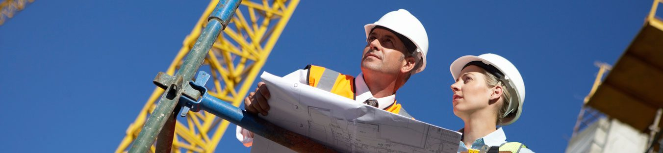 architects in hard hats with blueprints at construction site