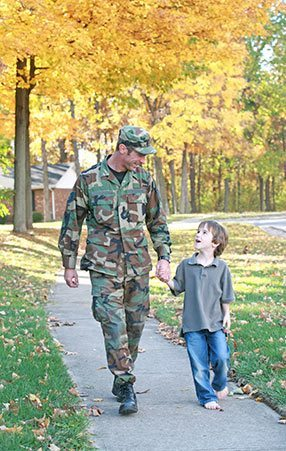 male soldier in fatigues holding boy's hand and walking