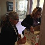 two staff members at Women's Assessment Center looking through boxes