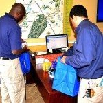 two volunteers from Glen Oaks Apartments packing toiletries into gift bags