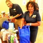 volunteers at Glen Oaks Apartments packing gift bags with toiletries