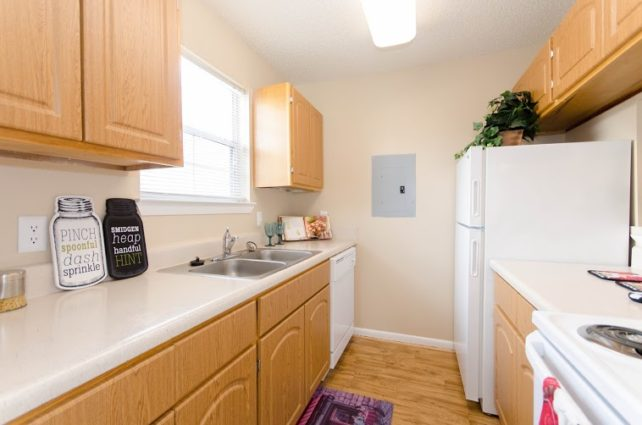 ROSS Management Services Kitchen with Fridge, Countertops, and Cabinets