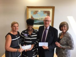 Four ROSS Companies Employees Hold Donation Checks for Local Charities