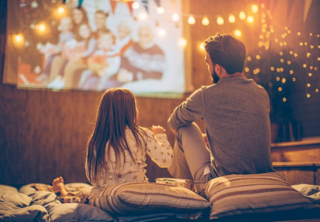 Father and daughter sitting at backyard and looking movie at home improved theatre. Backyard is decorated with string lights.