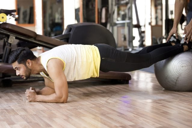 Fitness instructor with young man doing push-ups on Swiss ball at gym