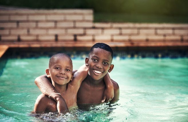 Shot of two young boys having fun together in a swimming pool
