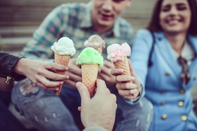 Smiling Teenage Friends Eating Ice Cream and Holding Cones in Hands
