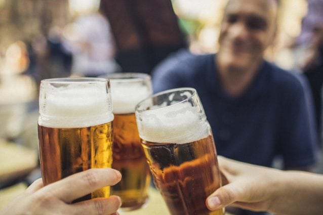 close up of beer glasses clinking between friends