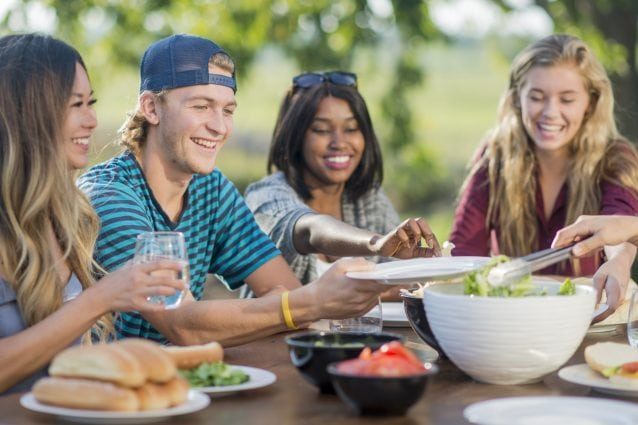 A multi-ethnic group of young men and women are outdoors at a backyard barbecue. They are wearing casual clothing. It is sunny. They are eating hot dogs and salad