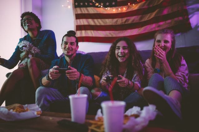 Young multi-ethnic friends eating fast food and playing video games