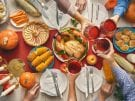 Happy Thanksgiving Day! Autumn feast. Family sitting at the table and celebrating holiday. Traditional dinner. Grandparents, parents and children. Hands and cheers. Top view.