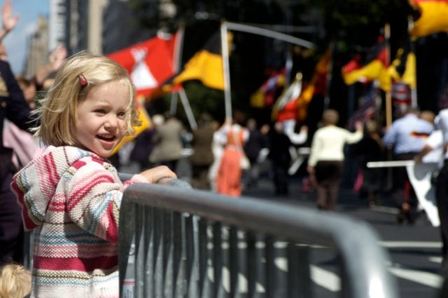 Little blond girl watches a parade go by