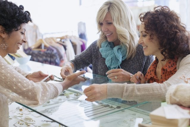 Store owner showing jewelry to two women.