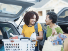 Mother helps college-age daughter unload car full of items.
