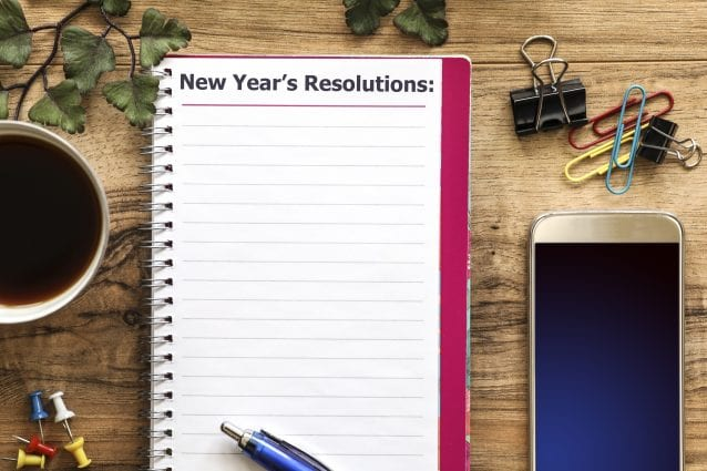 "Wooden office desk with items surrounding a ""New Year's Resolutions"" note pad. Group of objects includes: note pad, pen, fasteners, cup of coffee and cell phone. No people."