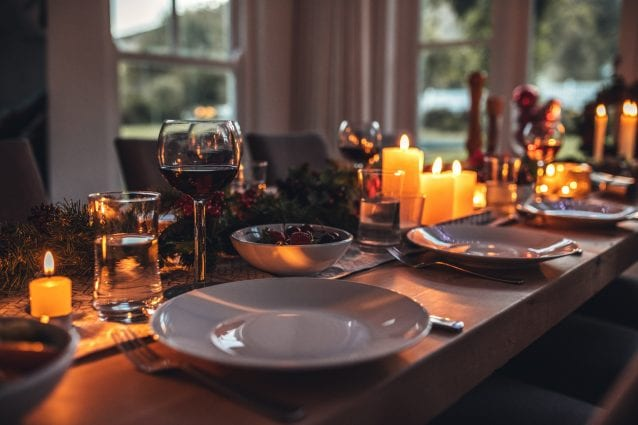Close up shot of holiday festive table with no people. Dining table with plates, wine glasses and candles.