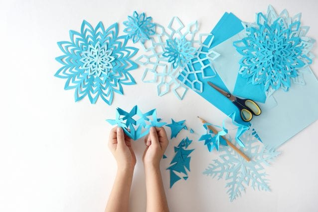 Making of snowflakes from paper. A traditional winter arts and crafts project