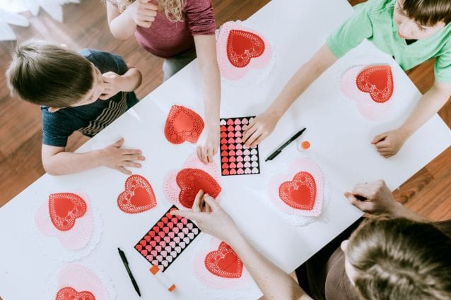 Children cut red and white paper Valentine's cards.