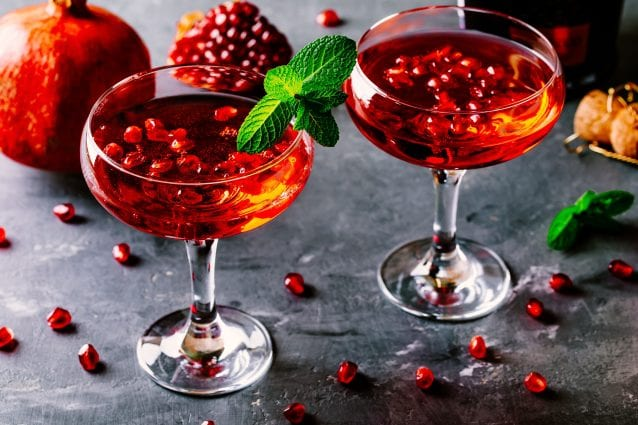 A pair of red, cranberry cocktails with mint garnish.